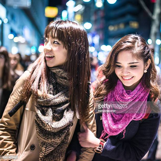 Asiatic friends togetherness on Tokyo embracing