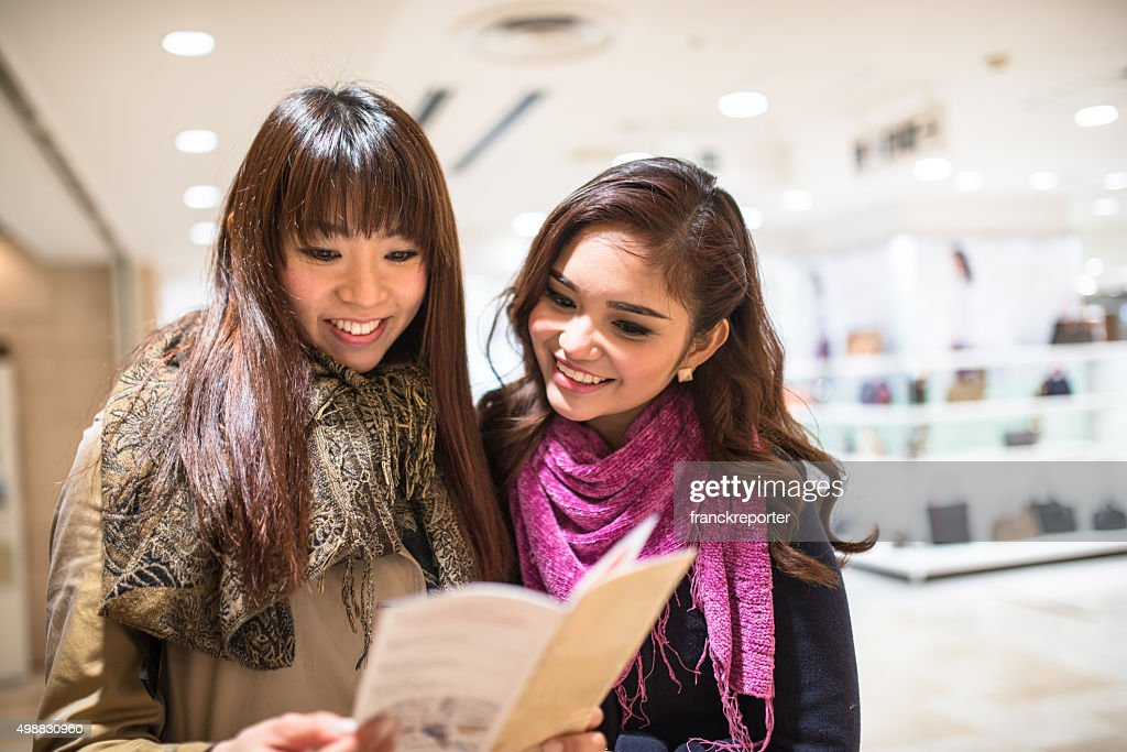 Asiatic friends togetherness on Tokyo reading the metro map : Stock Photo