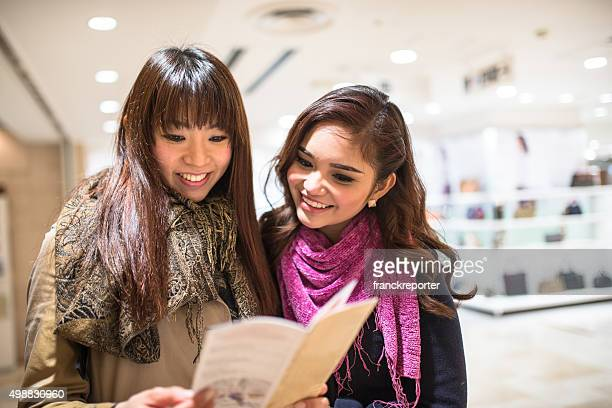 asiatic friends togetherness on tokyo reading the metro map - flyer leaflet stock photos and pictures