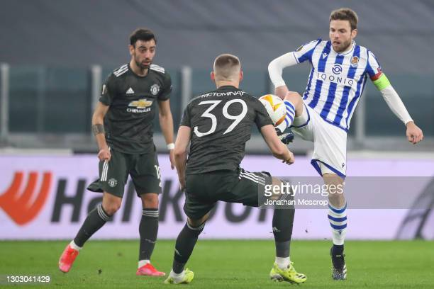 Asier Illarramendi of Real Sociedad chips the ball over the head of Scott McTominay of Manchester United as Bruno Fernandes looks on during the UEFA...