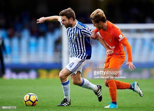 Asier Illarramendi of Real Sociedad duels for the ball with Sergio Gontan 'Keko' of Malaga CF during the La Liga match between Real Sociedad de...