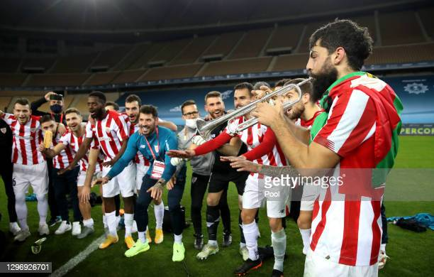 Asier Villalibre of Athletic Bilbao plays a trumpet in front of his team mates as they celebrate victory after the Supercopa de Espana Final match...