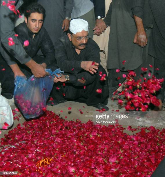 Asif Ali Zardari husband of former Pakistani premier Benazir Bhutto and his son Bilawal shower rose petals on the grave of Bhutto after her funeral...