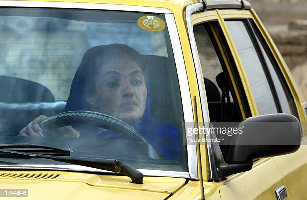Asina an Afghan woman who is one of 12 participating in a driving exam looks at the rear view mirror as she puts the car into reverse January 25 2003...