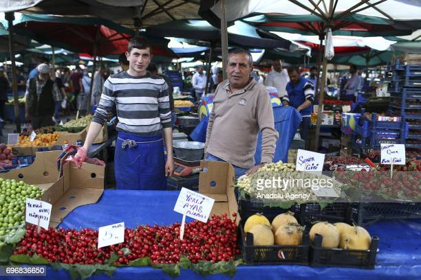 Asir Akdursun a greengrocer poses for a photo with his 18yearold greengrocer son Serhat Kahraman who had chosen the same field of profession with his...