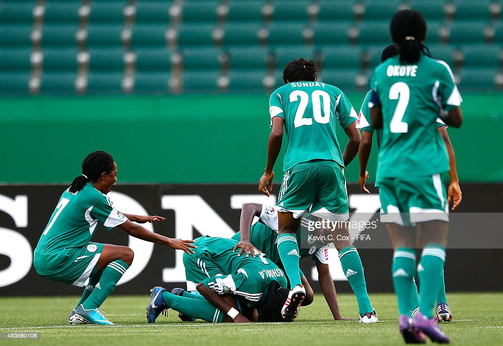 Asisat Oshoala (center) of Nigeria celebrates after scoring on a penalty kick against England during the FIFA U-20 Women's World Cup Canada 2014 Group C match between Nigeria and England at Commonwealth Stadium on August 13, 2014 in Edmonton, Canada.