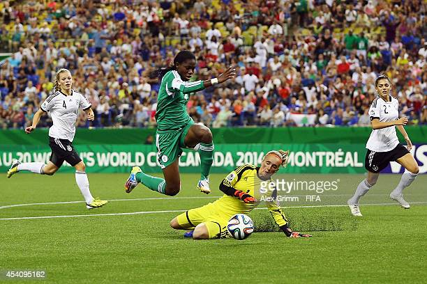 Asisat Oshoala of Nigeria is challenged by goalkeeper Meike Kaemper of Germany during the FIFA U20 Women's World Cup Canada 2014 final match between...