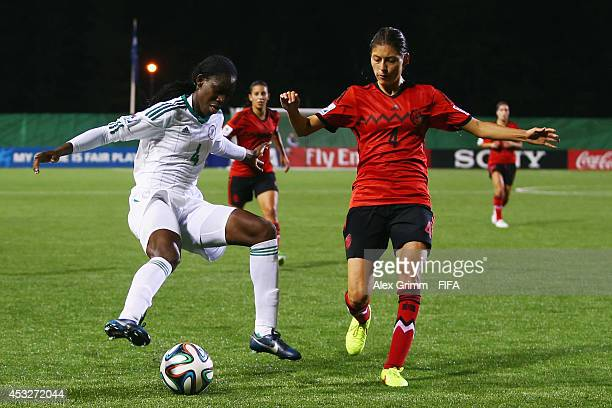 Asisat Oshoala of Nigeria is challenged by Paulina Solis of Mexico during the FIFA U20 Women's World Cup Canada 2014 group C match between Mexico and...