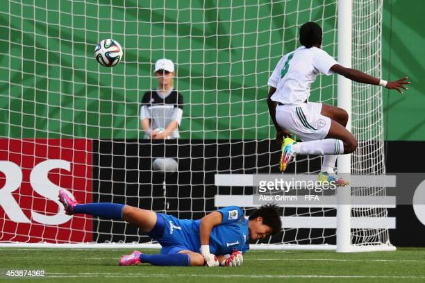 Asisat Oshoala of Nigeria scores her team's fifth goal against goalkeeper Kim Chol Ok of Korea DPR during the FIFA U20 Women's World Cup Canada 2014...