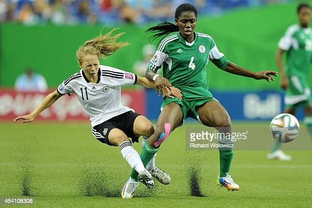 Asisat Oshoala of Nigeria trips Theresa Panfil of Germany during the FIFA Women's U20 Final at Olympic Stadium on August 24 2014 in Montreal Quebec...