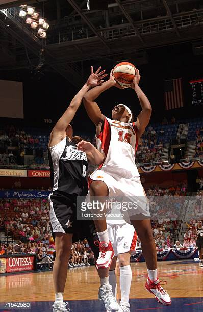 Asjha Jones of the Connecticut Sun goes to the basket against Jae Cross of the San Antonio Stars at Mohegan Sun Arena on July 30 2006 in Uncasville...