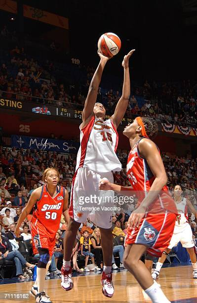 Asjha Jones of the Connecticut Sun goes to the basket against Monique Currie and Tangela Smith of the Charlotte Sting on June 3 2006 at Mohegan Sun...