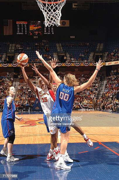Asjha Jones of the Connecticut Sun goes to the basket against Ruth Riley of the Detroit Shock in game three of the WNBA Eastern Conference Finals on...