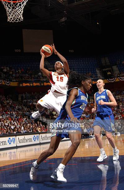 Asjha Jones of the Connecticut Sun goes to the basket against Shameka Christon of the New York Liberty during the game at Mohegan Sun on July 28 2005...