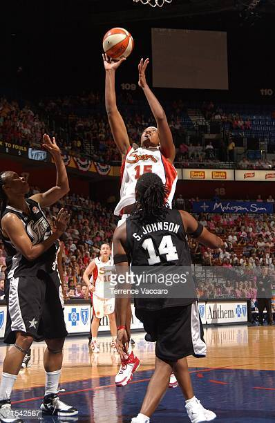 Asjha Jones of the Connecticut Sun goes to the basket against Shannon Johnson of the San Antonio Stars at Mohegan Sun Arena on July 30 2006 in...