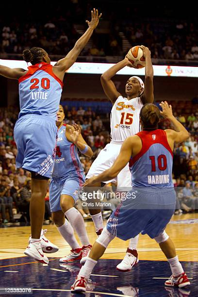 Asjha Jones of the Connecticut Sun shoots a jumper in the paint in front of Sancho Lyttle and Lindsey Harding of the Atlanta Dream in Game One of the...
