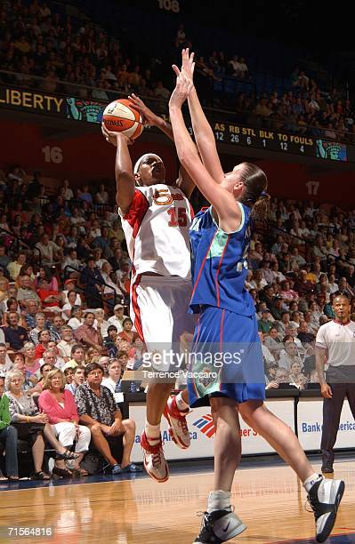 Asjha Jones of the Connecticut Sun shoots against Cathrine Kraayeveld of the New York Liberty on August 1 2006 at Mohegan Sun Arena in Uncasville...