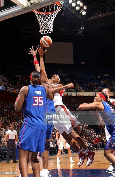 Asjha Jones the Connecticut Sun goes to the basket against Cheryl Ford and Deanna Nolan of the Detroit Shock at Mohegan Sun Arena in Uncasville...