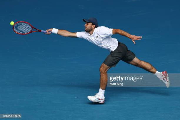 Aslan Karatsev of Russia plays a forehand in his Men's Singles fourth round match against Felix Auger-Aliassime of Canada during day seven of the...