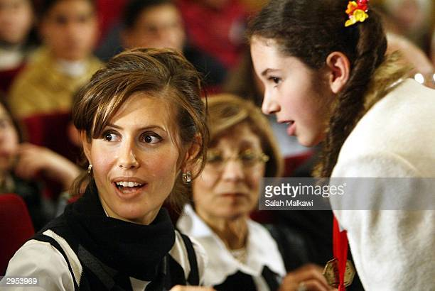 Asmaa alAssad wife of the Syrian President talks with a Syrian child as she attends the first national childhood conference February 9 2004 in Aleppo...