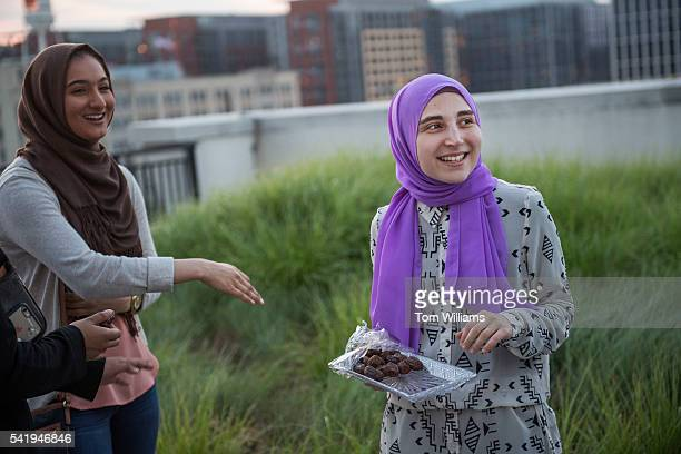 Asmaa Albaroudi right serves dates during an iftar dinner on a roof deck in Northeast for those who participated in fasting for Ramadan June 20 2016...
