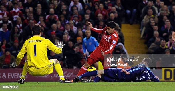 Asmir Begovic and Danny Higginbotham of Stoke feel the pressure of Luis Suarez of Liverpool during the Barclays Premier League match between...