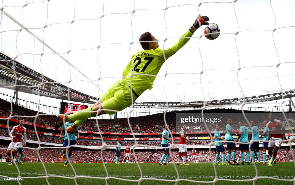 Asmir Begovic of AFC Bournemouth dives to make a save during the Premier League match between Arsenal and AFC Bournemouth at Emirates Stadium on September 9, 2017 in London, England.