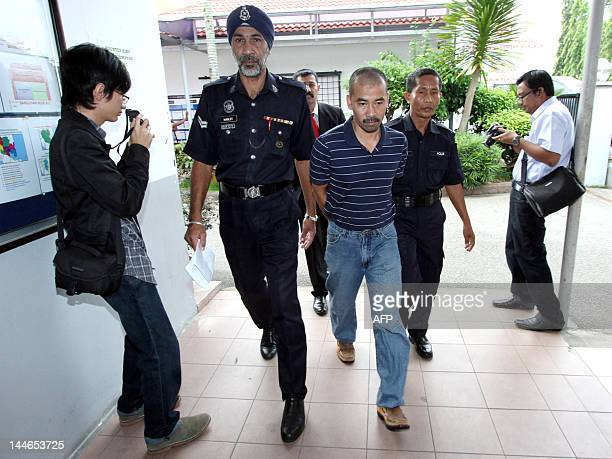 Asni Omar accused of murdering French tourist Stephanie Foray is escorted by Malaysian police as he arrives for trial at the High Court in Kuantan on...