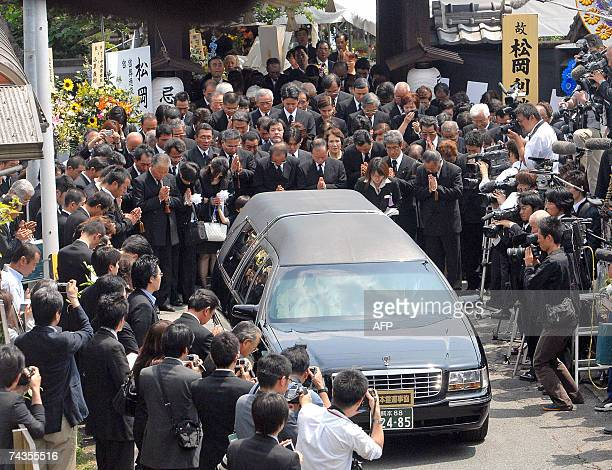 Hundreds of mourners pray as the hearse carrying the late Japanese Agriculture Forestry and Fisheries Minister Toshikatsu Matsuoka leaves a Buddhist...