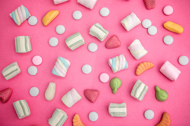 asorment of candies and sweets in pink background - 甜品 個照片及圖片檔