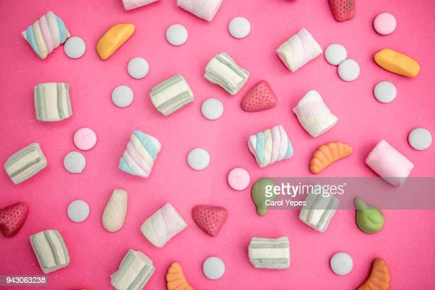asorment of candies and sweets in pink background - sweet food stock pictures, royalty-free photos & images