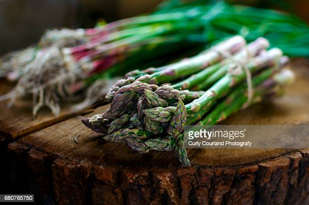 asparagus and garlic on the wooden board - rustikal stock-fotos und bilder