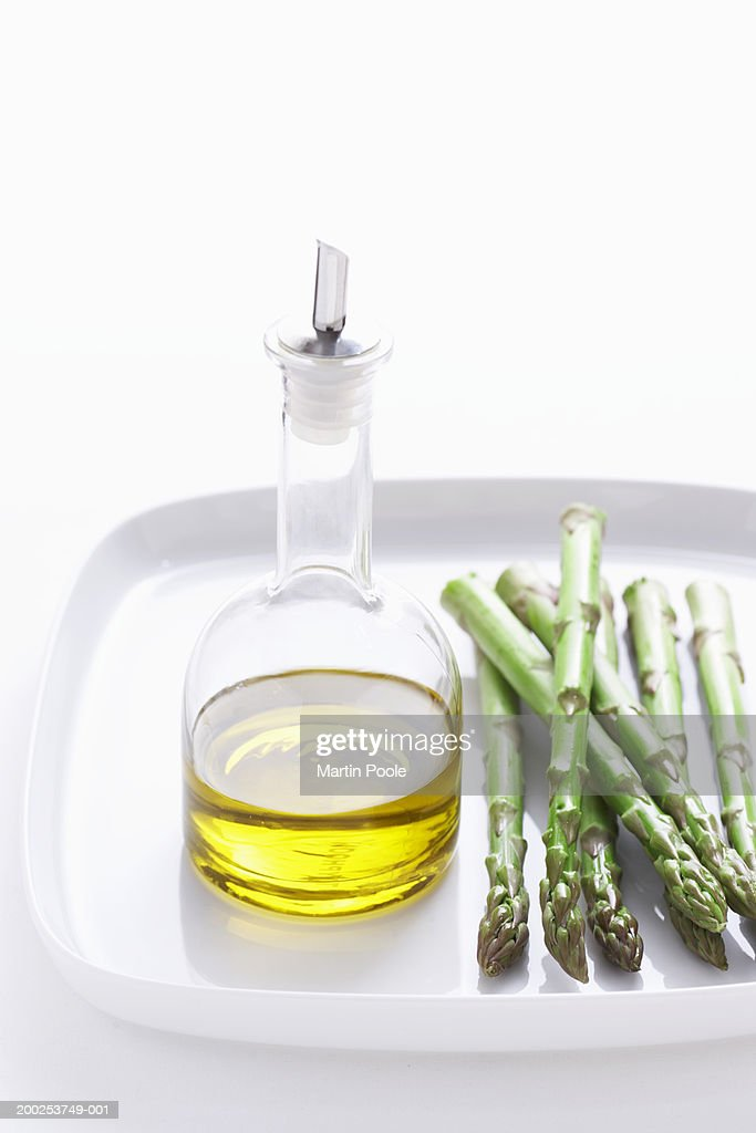 Asparagus and olive oil on plate, close-up : Stock Photo
