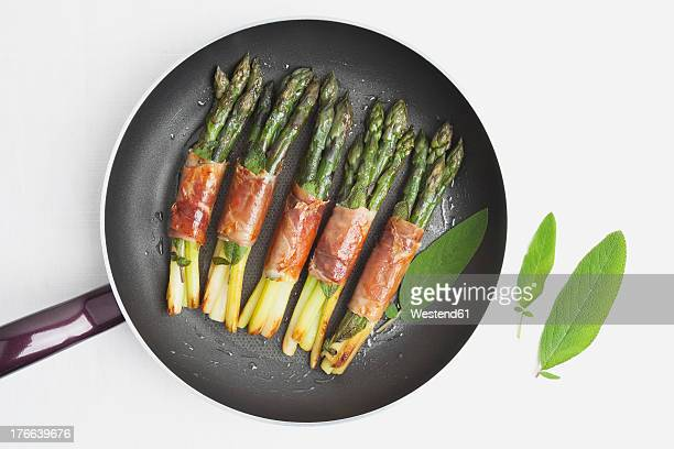 Asparagus with Saltimbocca, sage leaf and parma ham in frying pan