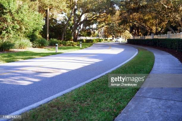 asphalt curved road with yellow dividing line - arman zhenikeyev stock pictures, royalty-free photos & images