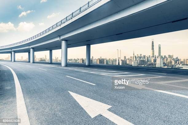 asphalt pavement highway with overpass bridge in front of huangpujiang near sunset. - flyover stock pictures, royalty-free photos & images