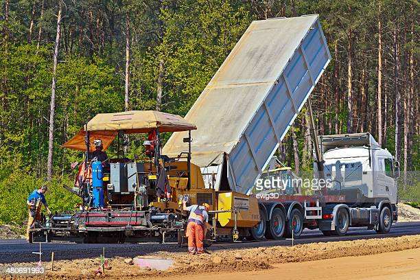 asphalt paving machine in highway construction - asphalt paving stock photos and pictures
