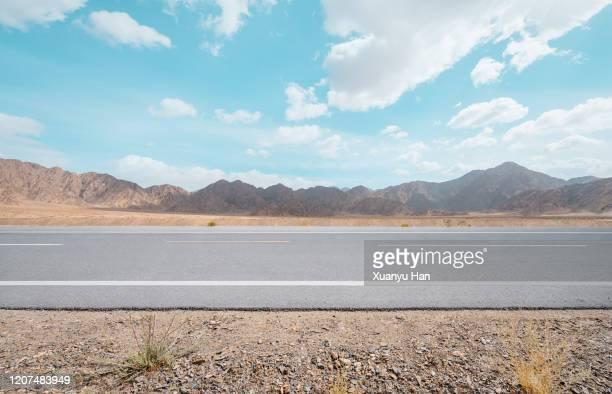 asphalt road in arid area - 境界線 ストックフォトと画像
