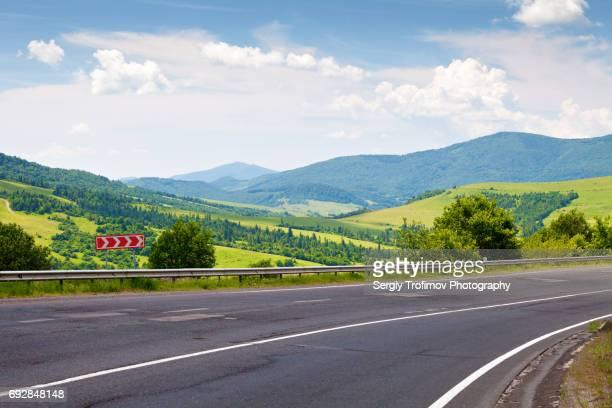 Asphalt road in green mountains, hills on background