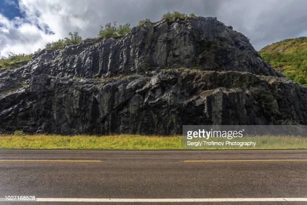 asphalt road in norway with wet rocks, side view - 人気のない道路 ストックフォトと画像