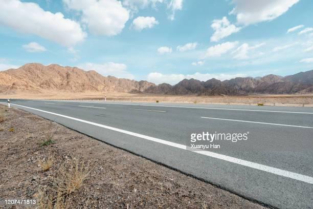 asphalt road through arid areas - 境界線 ストックフォトと画像