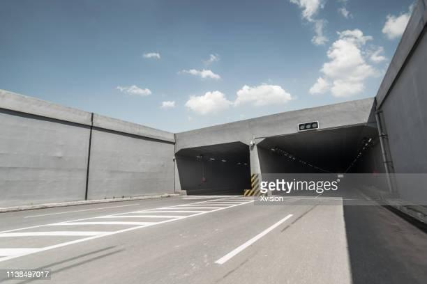 asphalt road under blue sky into tunnel for automobile commercial background - tunnel stock-fotos und bilder
