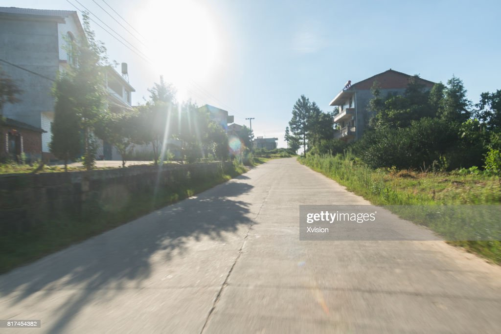 Asphalt road under blue sky with clouds in motion blur with plants in sides : Photo