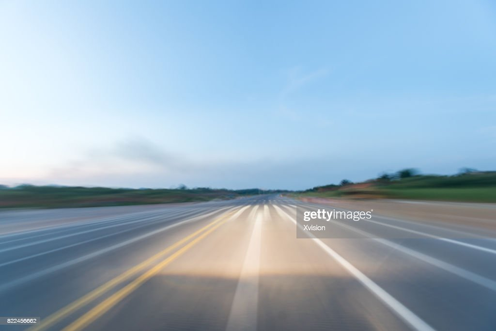 Asphalt road under blue sky with clouds in motion blur with plants in sides : Stock Photo