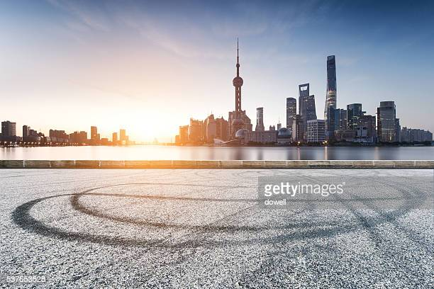 asphalt road with car tracks with cityscape and skyline of shanghai at sunrise