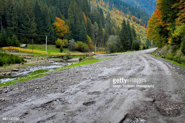 asphalt road with potholes in mountains - rough stock pictures, royalty-free photos & images