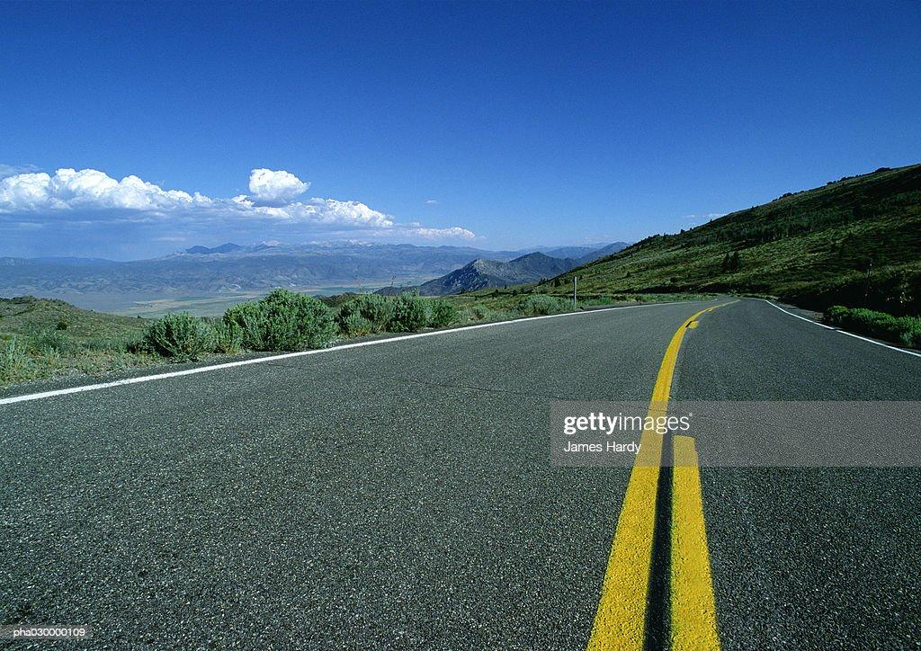 Asphalt road with yellow lines overlooking mountainous region. : Stockfoto