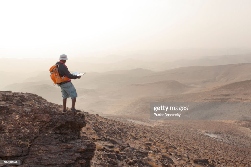 Aspirations for adventure. Reading map and looking on horizon over desert landscape. : Stock Photo