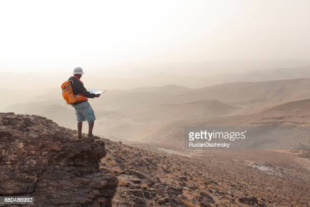 Aspirations for adventure. Reading map and looking on horizon over desert landscape.