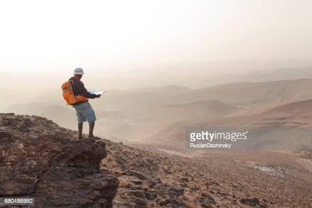 Aspirations pour l'aventure. Lecture de carte et donnant sur l'horizon sur le paysage désertique.